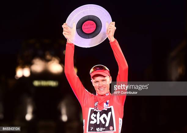 Team Sky's British cyclist Chris Froome raises his trophy as he celebrates on the podium winning the 72nd edition of La Vuelta Tour of Spain cycling...