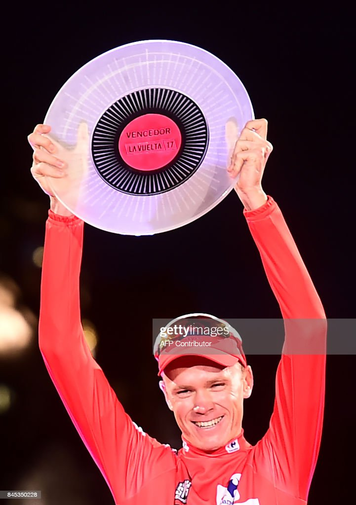 Team Sky's British cyclist Chris Froome raises his trophy as he celebrates on the podium winning the 72nd edition of 'La Vuelta' Tour of Spain cycling race, in Madrid, on September 10, 2017. Chris Froome became just the third rider in history to win the Vuelta a Espana and Tour de France in the same year as Matteo Trentin won the 21st stage of the Vuelta through the centre on Madrid on Sunday. /