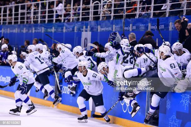 Team Slovenia rushes the ice after an overtime win of a men's preliminary round ice hockey match between the United States and Slovenia during the...