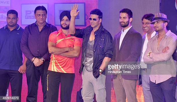 Team Speedy Singhs coowner Akshay Kumar and team Yo Yo Tigers coowner Yo Yo Honey Singh with kabaddi players during the unveiling of league...