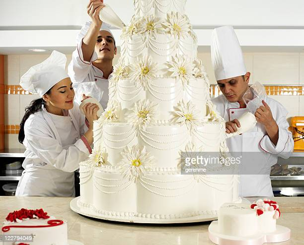 team spirit in pastry - decorating a cake stock pictures, royalty-free photos & images