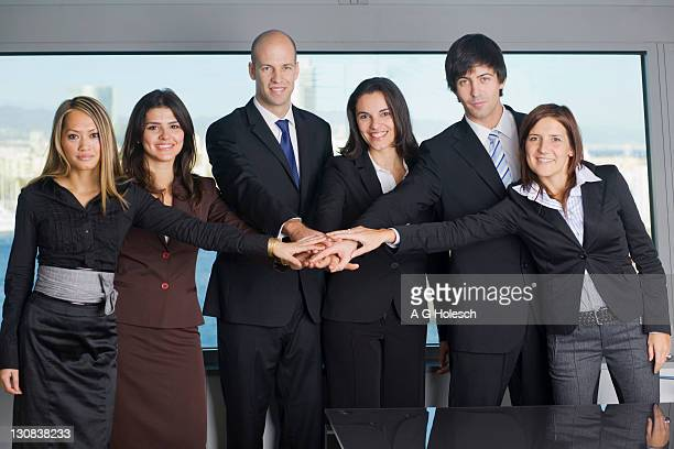 Team spirit, six business people putting their hands together