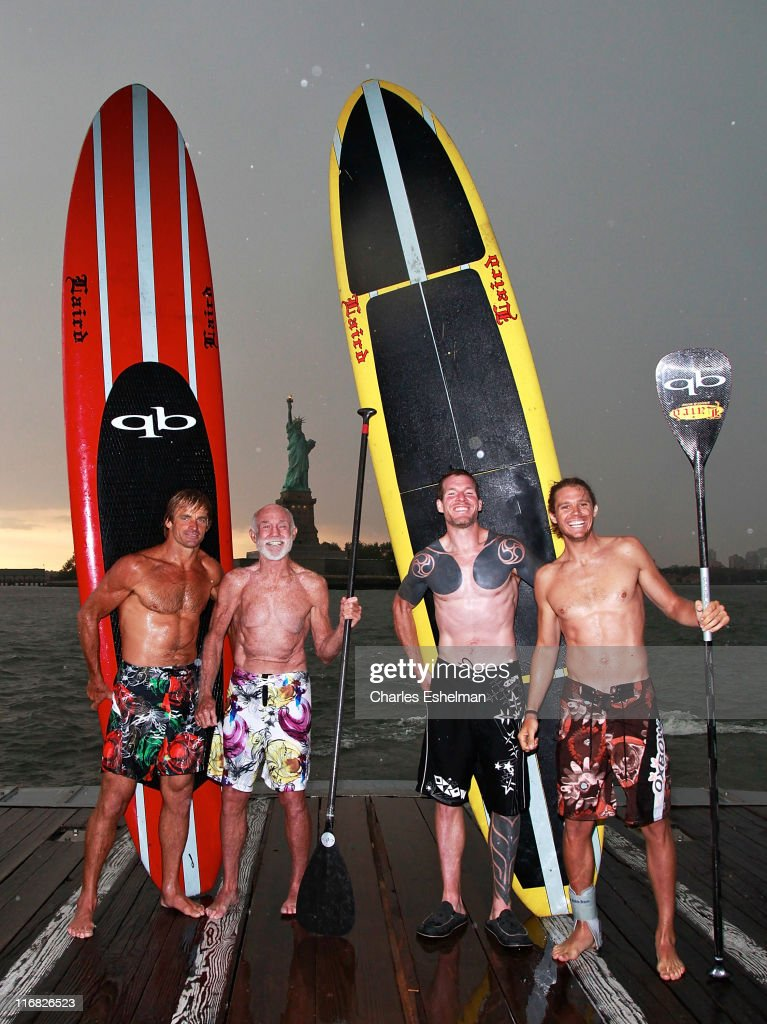 Team Surfing USA's Laird Hamilton, Don Wildman, Tim Commerford and Jason Winn relax at the completion of his cross-country relay race at the Statue of Liberty on June 26, 2009 in New York City.
