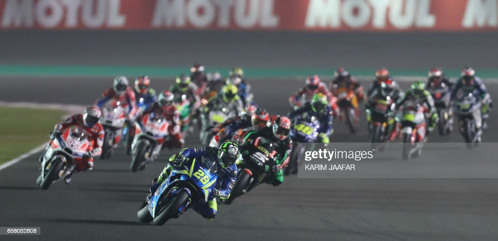 Team SUZUKI ECSTAR's Italian rider Andrea Iannone (front) competes during the 2017 Qatar MotoGP at the Losail International Circuit, north of the capital Doha on March 26, 2017. Spain's Maverick Vinales of Movistar Yamaha MotoGP won the season-opening Qatar MotoGP on March 26, 2017, shrugging off a poor start from pole position under the desert floodlights. Defending world champion Marc Marquez was fourth on a Honda. / AFP PHOTO / Karim JAAFAR