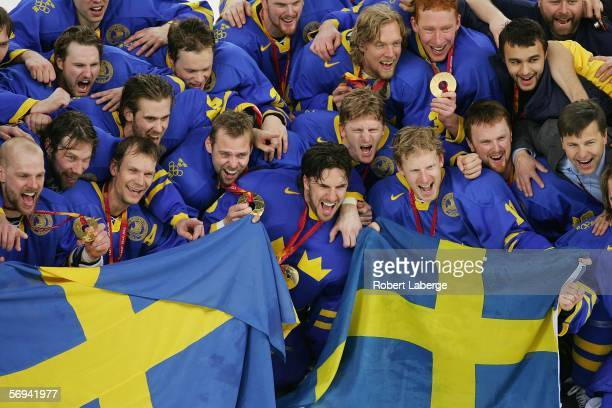 Team Sweden poses for photographers with their gold medals after defeating Finland 32 in the final of the men's ice hockey match between Finland and...