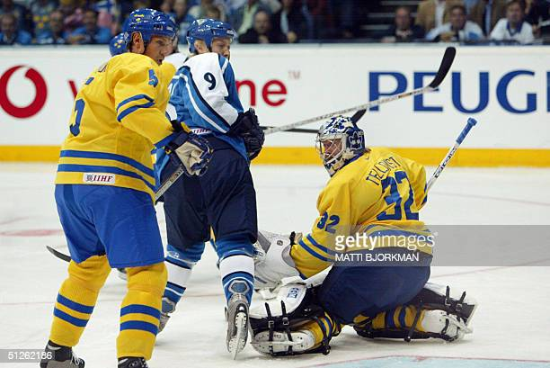 Team Sweden's Nicklas Lidstrom and team Finland's Niklas Hagman watch the puck go past Sweden goalkeeper Mikael Tellqvist during the first period of...