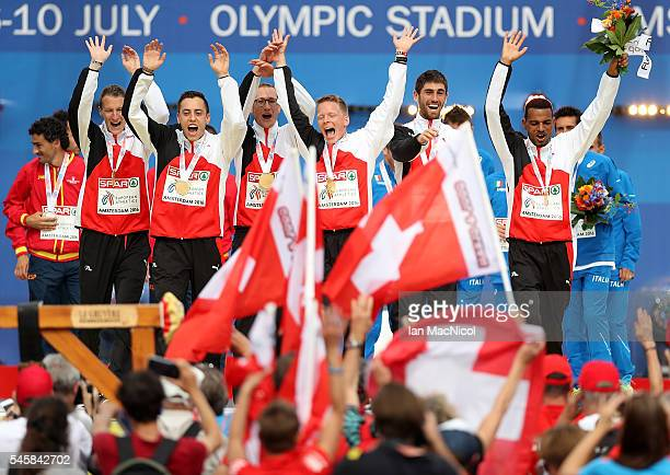Team Switzerland celebrate after winning the team cup in the mens half marathon on day five of The 23rd European Athletics Championships at Olympic...