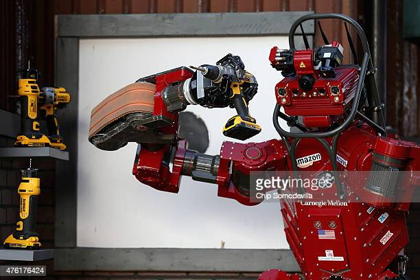 Team Tartan Rescue's CHIMP robot uses a handheld power tool during the cutting task of the Defense Advanced Research Projects Agency Robotics...