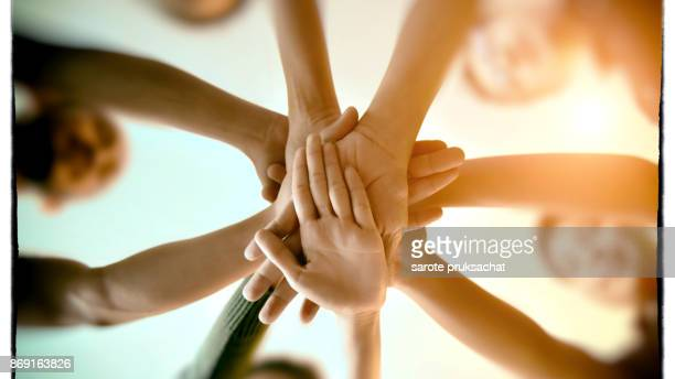team teamwork join hands partnership concept . - achievement stock pictures, royalty-free photos & images