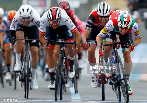 Team UAE Emirates rider Colombia's Fernando Gaviria compete the final sprint flanked by Team Deceuninck rider Italy's Elia Viviani during the stage...