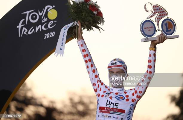 Team UAE Emirates rider Slovenia's Tadej Pogacar celebrates on the podium after winning the best climber's polka dot jersey of the 107th edition of...