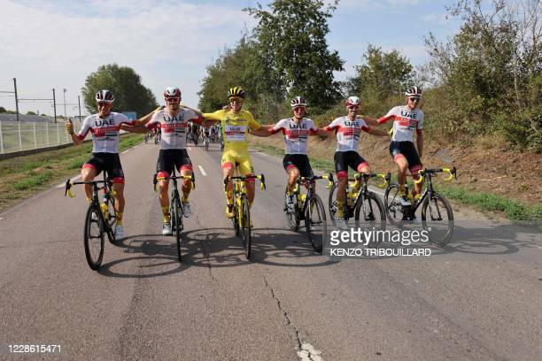 Team UAE Emirates rider Slovenia's Tadej Pogacar wearing the overall leader's yellow jersey and Team UAE Emirates riders ride during the 21st and...