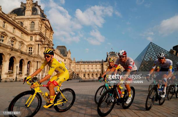 Team UAE Emirates rider Slovenia's Tadej Pogacar wearing the overall leader's yellow jersey rides in the pack in front of the Louvre pyramid and...