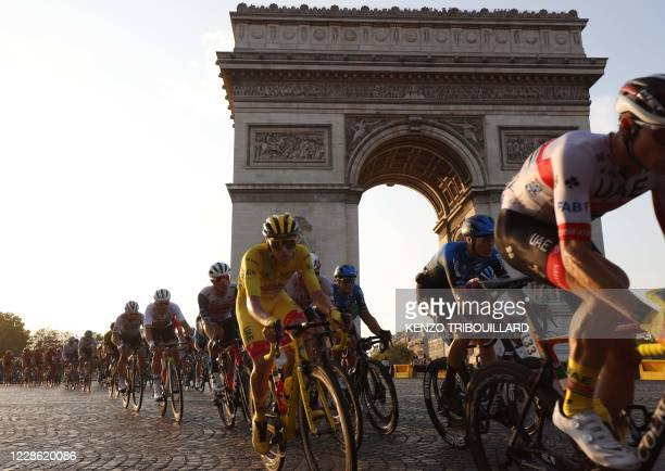 Team UAE Emirates rider Slovenia's Tadej Pogacar wearing the overall leader's yellow jersey rides on the Champs Elysees avenue with the Arc de...