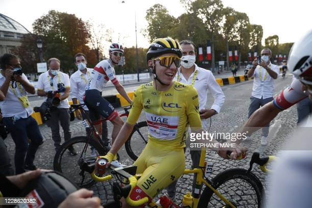 Team UAE Emirates rider Slovenia's Tadej Pogacar wearing the overall leader's yellow jersey celebrates after winning the 107th edition of the Tour de...