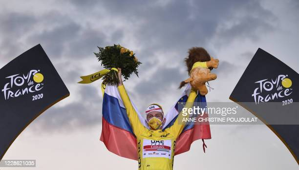 Team UAE Emirates rider Slovenia's Tadej Pogacar wearing the overall leader's yellow jersey celebrates on the podium after winning the 107th edition...