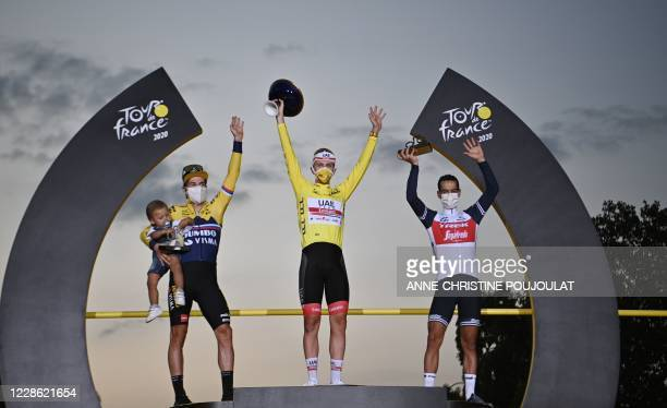 Team UAE Emirates rider Slovenia's Tadej Pogacar wearing the overall leader's yellow jersey celebrates on the podium between Team Jumbo rider...