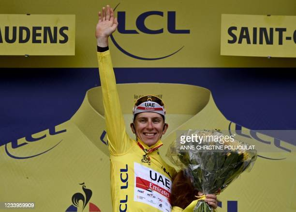 Team UAE Emirates' Tadej Pogacar of Slovenia celebrates his overall leader yellow jersey on the podium at the end of the 16th stage of the 108th...