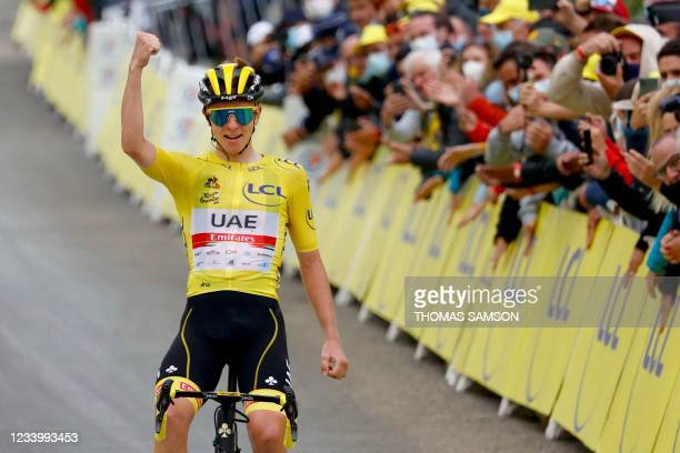 Team UAE Emirates' Tadej Pogacar of Slovenia wearing the overall leader's yellow jersey celebrates as he crosses the finish line during the 18th...