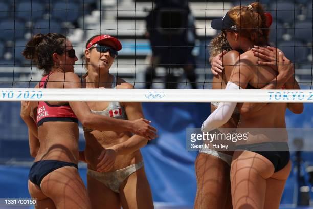 Team United States and Team Canada embrace after the Women's Round of 16 beach volleyball on day nine of the Tokyo 2020 Olympic Games at Shiokaze...