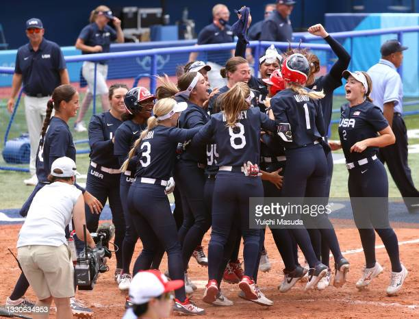 Team United States players celebrate with teammate Kelsey Stewart after she hit a walk-off home run to win the game 2-1 against Team Japan during...