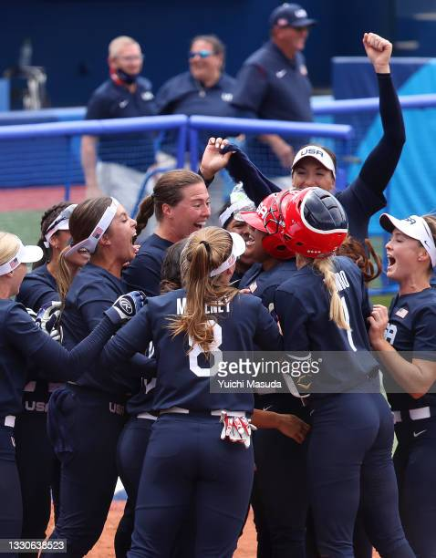 Team United States players celebrate with teammate Kelsey Stewart after she hit a walk-off home run to win the game 2-1 in the seventh inning against...