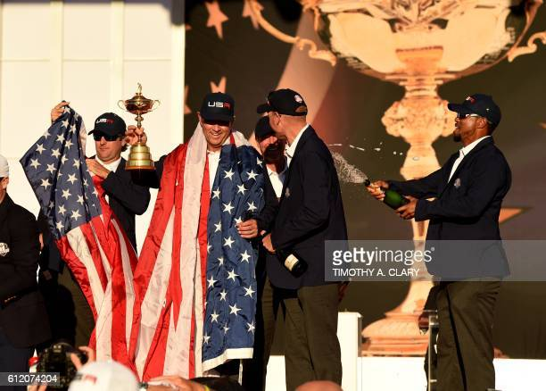 TOPSHOT Team USA Captain Davis Love III and Vice Captain Tiger Woods celebrate during the trophy ceremony after the Singles Matches during the 41st...