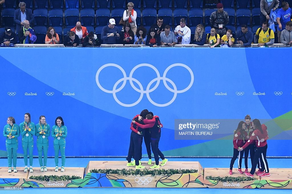 Team USA celebrate on the podium after they won the gold medal ahead of Team Australia (L) and Team Canada in the Women's 4x200m Freestyle Relay Final during the swimming event at the Rio 2016 Olympic Games at the Olympic Aquatics Stadium in Rio de Janeiro on August 10, 2016. / AFP / Martin BUREAU