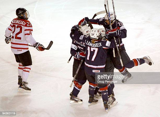 Team USA celebrates a third period goal by Karen Thatcher as Hayley Wickenheiser of Canada skates by during their Women's Ice Hockey match at the...