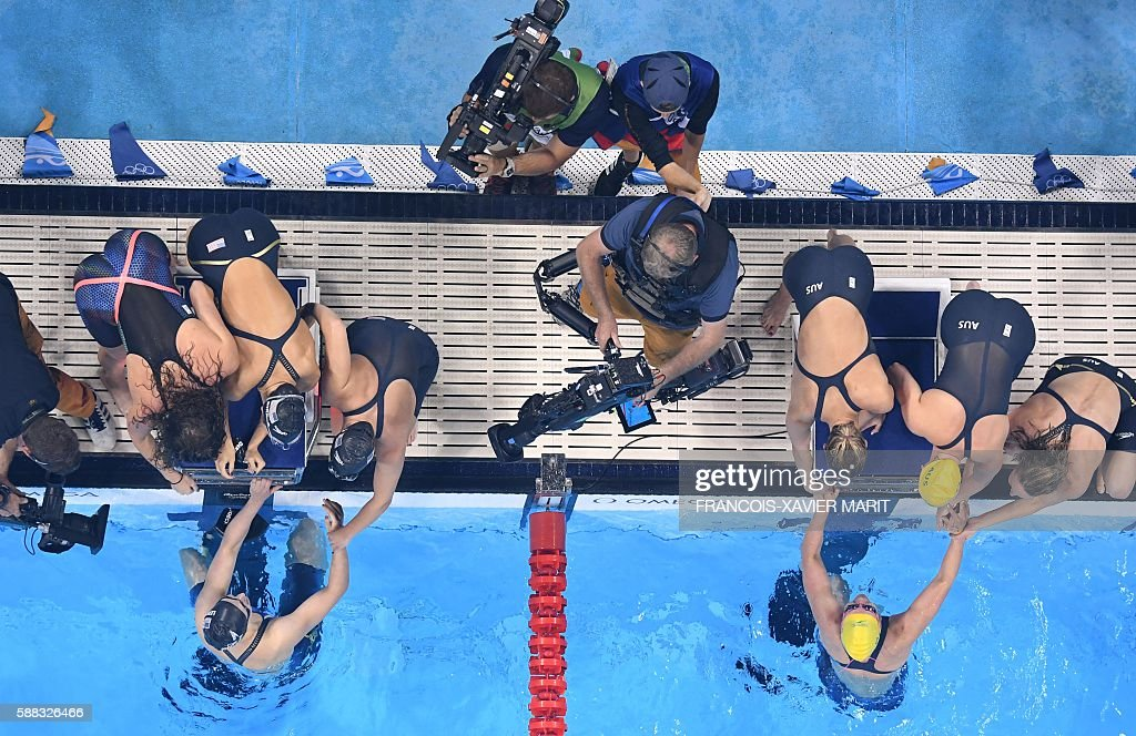 Team USA (L) gold, and team Australia, silver, celebrate after winning the Women's 4x200m Freestyle Relay Final during the swimming event at the Rio 2016 Olympic Games at the Olympic Aquatics Stadium in Rio de Janeiro on August 10, 2016. / AFP / François-Xavier MARIT