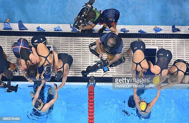 Team USA gold and team Australia silver celebrate after winning the Women's 4x200m Freestyle Relay Final during the swimming event at the Rio 2016...
