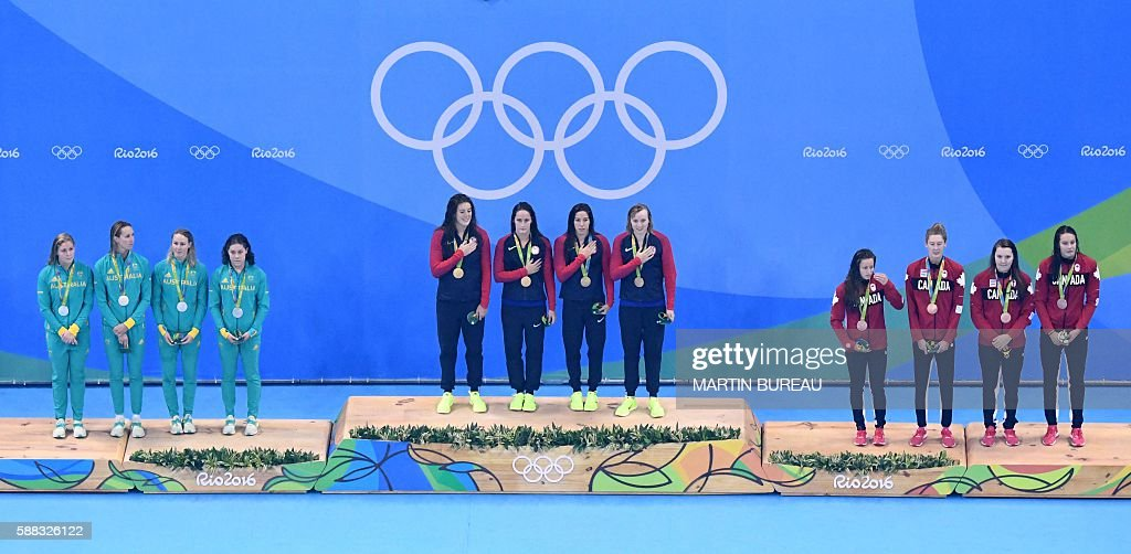 Team USA listen to their national anthem on the podium after they won the gold medal ahead of Team Australia (L) and Team Canada in the Women's 4x200m Freestyle Relay Final during the swimming event at the Rio 2016 Olympic Games at the Olympic Aquatics Stadium in Rio de Janeiro on August 10, 2016. / AFP / Martin BUREAU