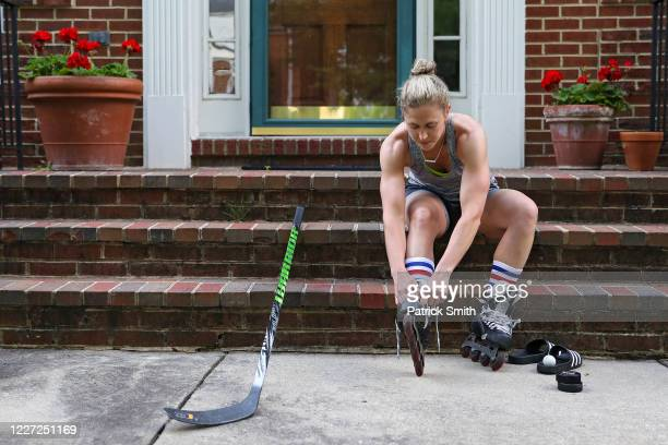 Team USA Olympic Women's Hockey Gold Medalist Haley Skarupa laces up rollerblades before she performs stickhandling drills in her driveway during a...