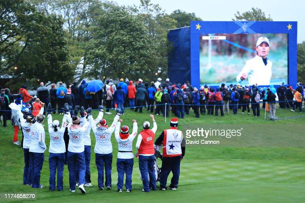 Team USA players watch a screen as Danielle Kang of Team USA wins her match during Day 2 of the Solheim Cup at Gleneagles on September 14 2019 in...