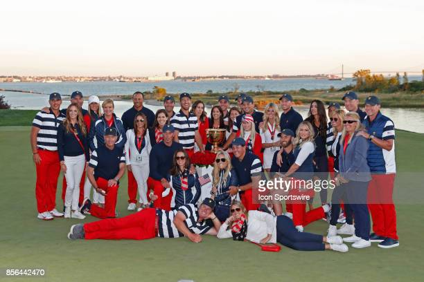 Team USA poses for a group photo with their wives and girlfriends after winning the Presidents Cup after the final round of the Presidents Cup at...