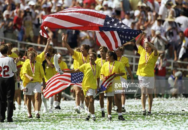 Team USA wave flags as they walk across the field in celebration of their victory over Team China in the Championship match of the FIFA Women's World...