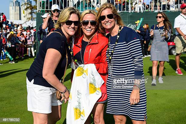 Team USA wives and girlfriends from left Kim Barclay Amy Mickelson and Tabitha Furyk pose for a photo during the first round of The Presidents Cup at...