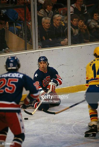 Team USA's Mark Pavelich struggles to make a pass to Buzz Schneider during the XIII Olympic Winter Games against team Sweden in February of 1980 in...
