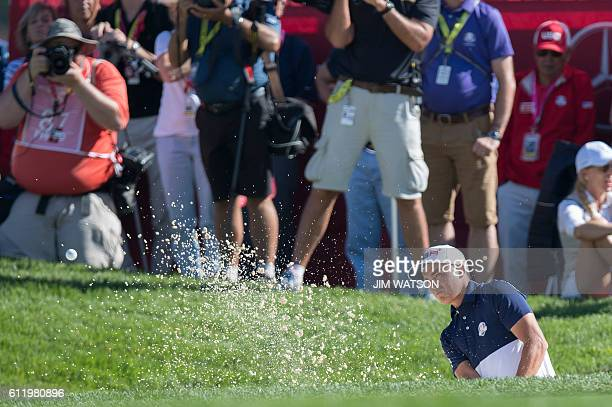Team USA's Rickie Fowler swings from the bunker during the singles matches at Hazeltine National Golf Course in Chaska Minnesota on October 2 during...