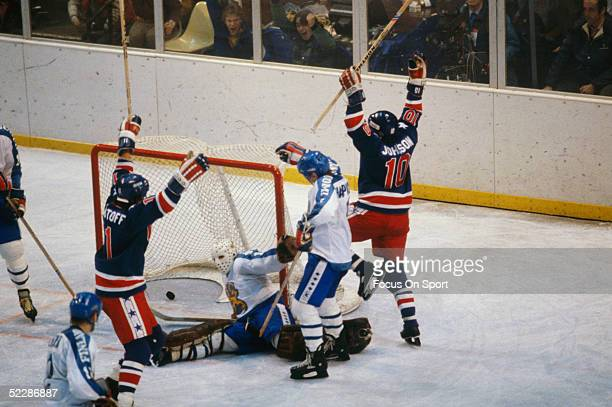 Team USA's Steve Christoff and Mark Johnson raise their sticks in the air after scoring against Team Finland during the XIII Olympic Winter Games in...