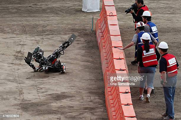 Team Valor's semiautonomous ESCHER robot falls backwards during its first run during the Defense Advanced Research Projects Agency Robotics Challenge...