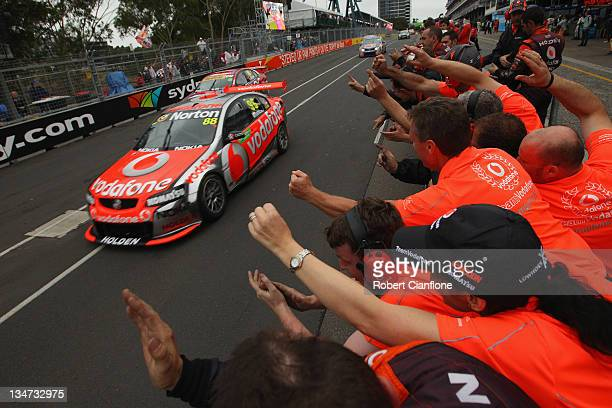Team Vodafone crew members celebrate after Jamie Whincup driver of the Team Vodafone Holden won the championship at the Sydney 500 which is round 14...
