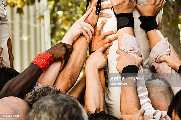 team work. castellers hands building a human tower - castellers stock photos and pictures