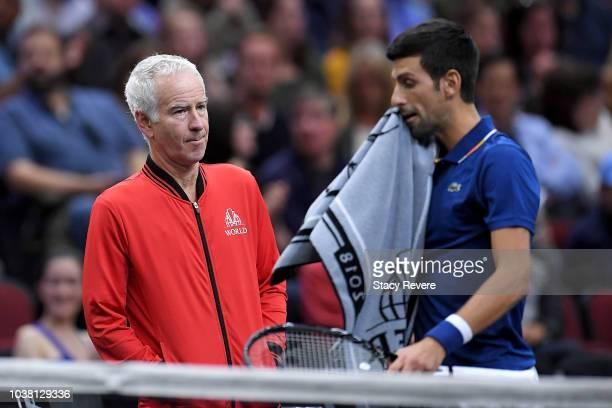 Team World Captain John McEnroe of the United States looks at Team Europe Novak Djokovic of Serbia during his Men's Singles match against Team World...