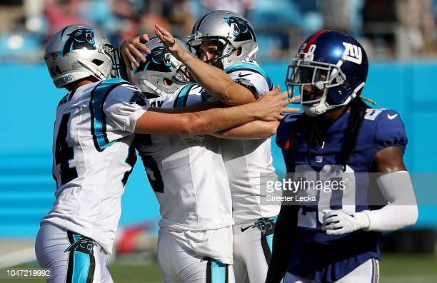 Teamamtes JJ Jansen and Michael Palardy celebrate with Graham Gano of the Carolina Panthers after he made a 63 yard field goal to win the game as...