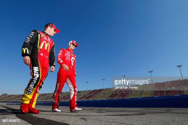Teamates Kyle Larson driver of the Target Chevrolet and Jamie McMurray driver of the McDonald's Chevrolet walk down pit lane during qualifying for...