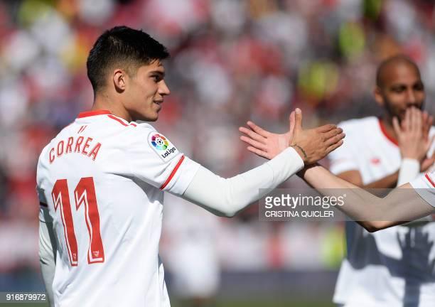 A teammate congratulates Sevilla's Argentinian midfielder Joaquin Correa after scoring a goal during the Spanish league football match between...