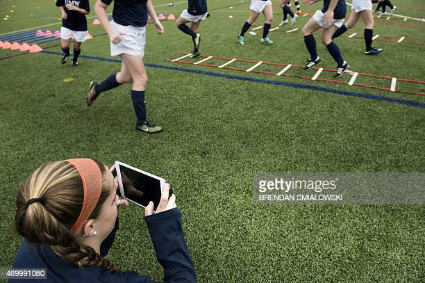 Teammate uses an iPad to record fellow members of the University of Mary Washington Women's Soccer team as they perform drills during a practice...