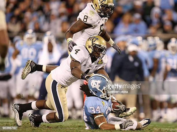 Teammates Adam Gunn and Elijah Fields of the Pittsburgh Panthers tackle Johnny White of the North Carolina Tar Heels during their game on December 26...