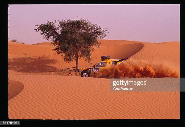 Teammates Ambrosino and Baumgartner drive their car a Peugeot 205 T16 through the Mauritanian desert during the 1990 Paris Dakar Rally NemaTidjika...